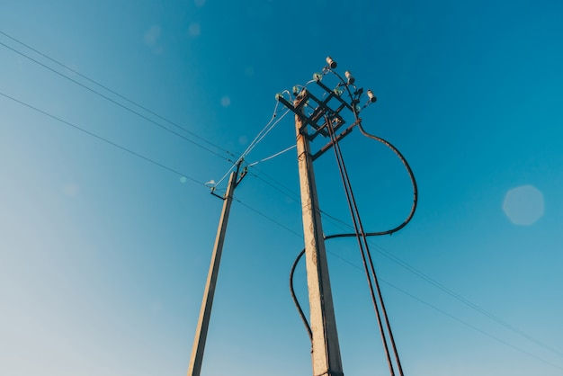 Lignes électriques de gros plan de ciel bleu. moyeu électrique sur poteau. matériel électrique avec espace copie. fils de haute tension dans le ciel. l'industrie de l'électricité.