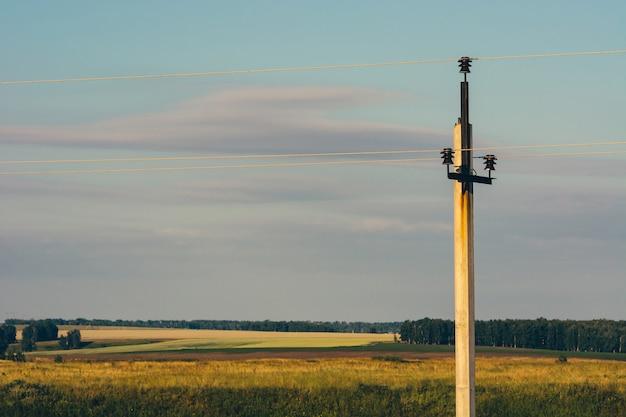 Les lignes électriques passent à travers les champs jaunes. pilier électrique dans le champ sous le ciel bleu. fils haute tension dans le ciel.