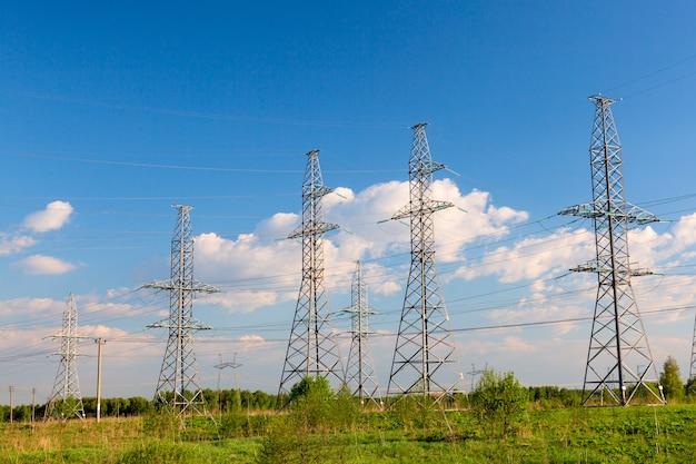Lignes électriques et pylônes contre ciel bleu.