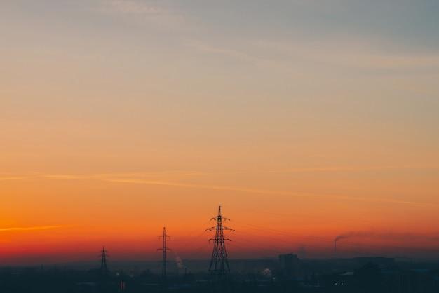 Lignes électriques en ville à l'aube. silhouettes de bâtiments urbains parmi le smog au lever du soleil. câbles de haute tension sur ciel jaune orange chaud. industrie électrique au coucher du soleil. alimentation électrique de la ville. contexte urbain de brume.