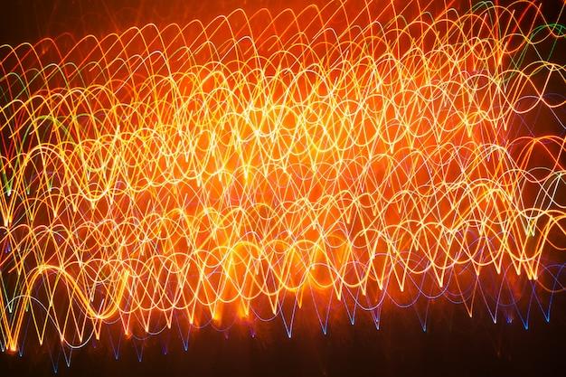 Lignes rougeoyantes multicolores ondulées sur un fond sombre, coup longue exposition