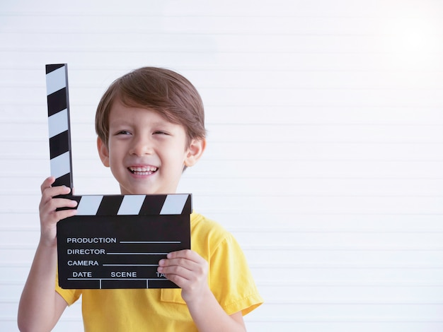 Liitle caucasian boy holding filme making clapper board with smile.