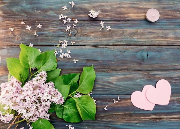 Lilas, bougie violette et deux coeurs roses sur fond de bois vintage