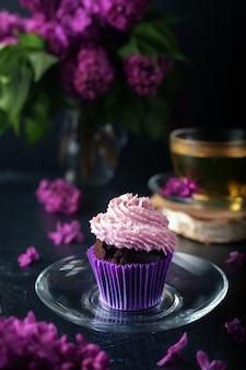 Lilas, muffins à la crème de caillé crémeux avec une tasse de thé