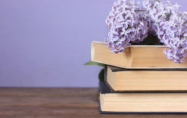 Lilas et une pile de livres sur la table. espace de copie. espace vide pour votre texte.
