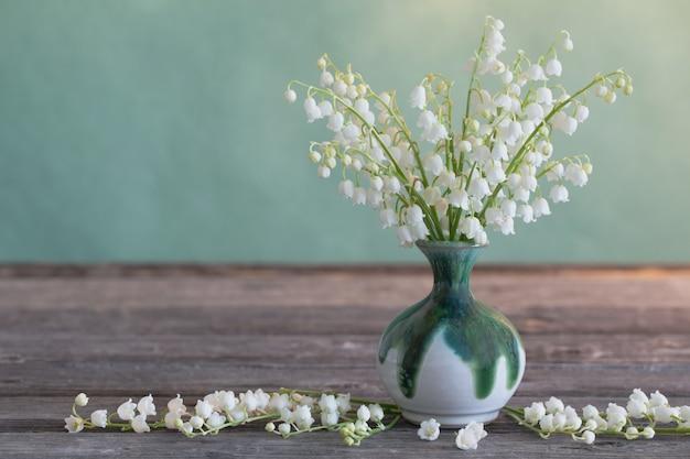 Lilly de vallée dans un vase sur une table en bois