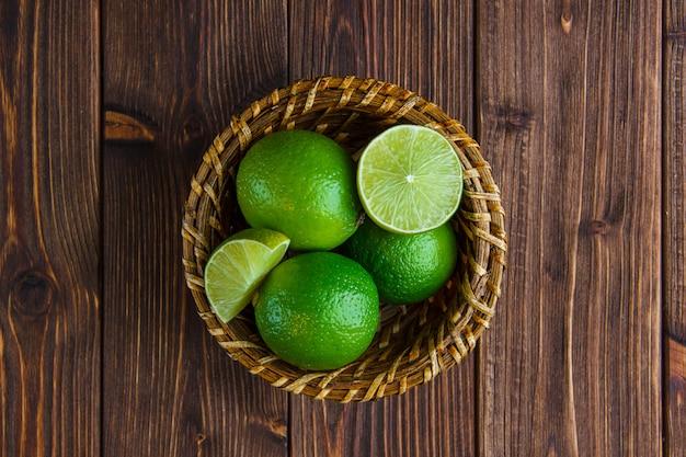 Limes dans un panier en osier sur table en bois. pose à plat.