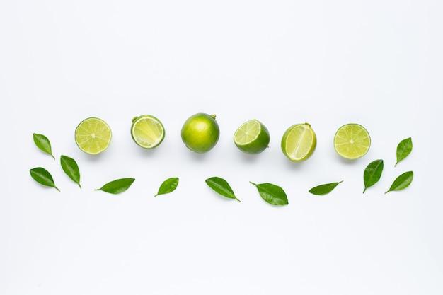 Limes avec des feuilles isolées sur une surface blanche.