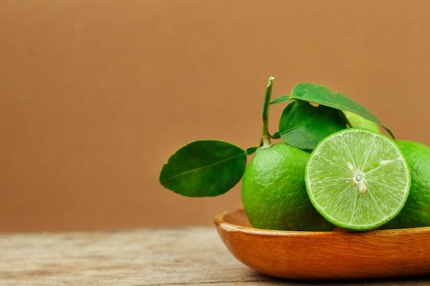 Limes fraîches dans un bol en bois sur fond en bois
