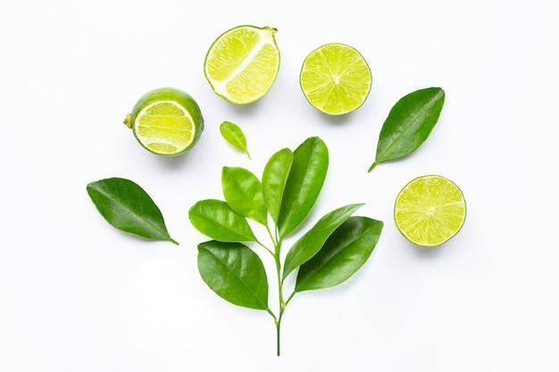 Limes fraîches avec des feuilles isolés sur blanc