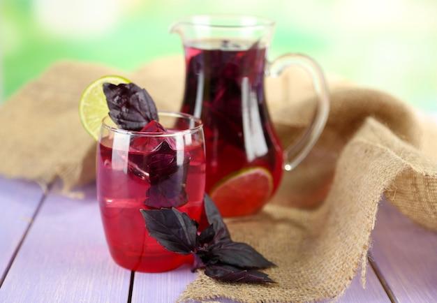 Limonade au basilic rouge en cruche et verre sur table en bois