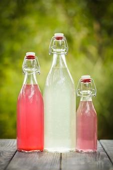 Limonade aux baies dans les bouteilles sur la table à l'extérieur