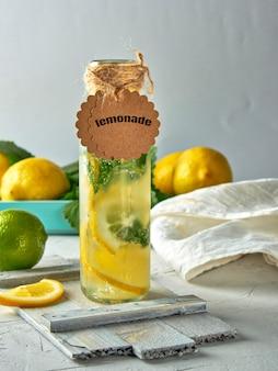 Limonade aux citrons, feuilles de menthe, citron vert dans une bouteille en verre