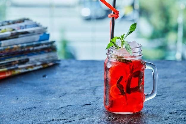 Limonade aux fraises avec glace, menthe paille dans la surface sombre