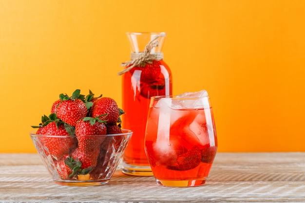 Limonade aux fraises en pot et verre sur fond en bois et jaune, vue latérale.