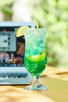 Une limonade aux fruits à côté d'un ordinateur portable sur une table en bois