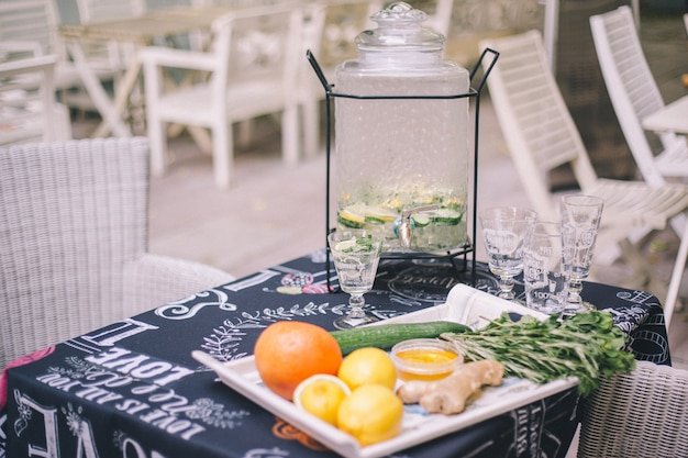 Limonade citron-concombre dans la limonade. devant lui sont des ingrédients de fruits sur un plateau.