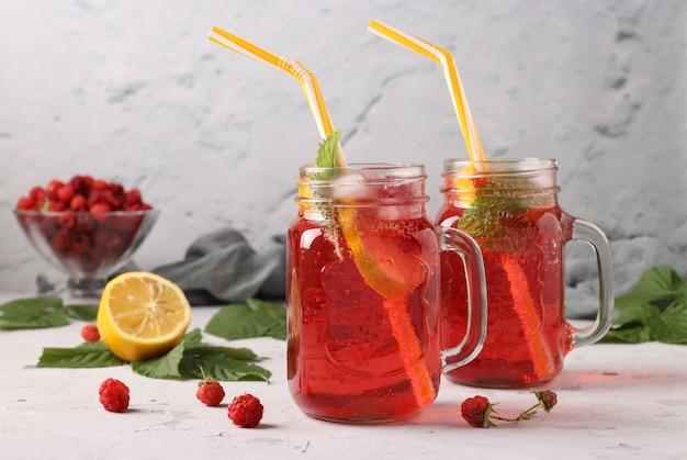 Limonade ou cocktail aux framboises, glace au citron sur table en béton gris