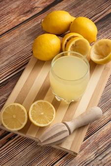 Limonade dans une tasse en verre sur la planche de bois, vue du dessus