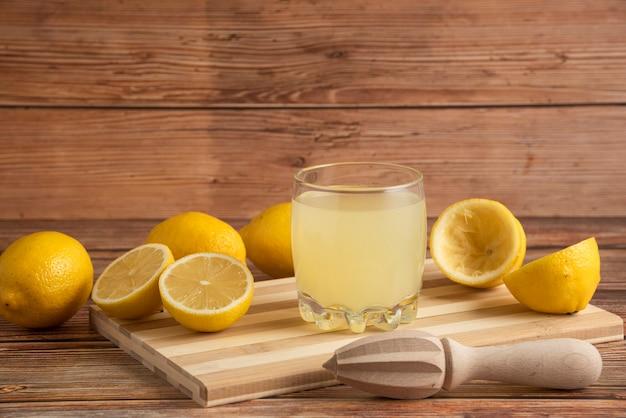 Limonade dans une tasse en verre sur la planche de bois