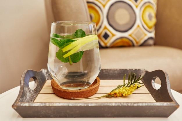 Limonade dans une tasse en verre avec des tranches de citron et de feuilles de menthe, un plateau avec un brin de plantes