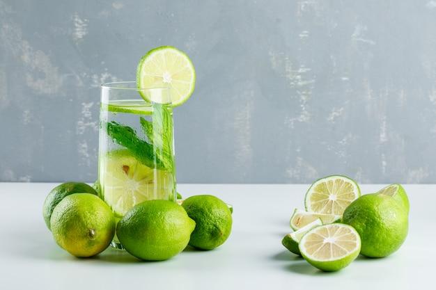 Limonade dans un verre avec des citrons, vue latérale des herbes sur blanc et plâtre