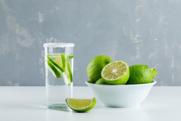 Limonade dans un verre avec vue de côté de citrons sur blanc et plâtre