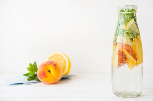 Limonade détox maison au citron et pêche dans une bouteille