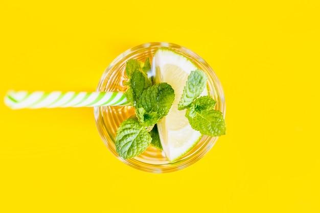 Limonade d'été à l'eau, citron vert et menthe avec une paille