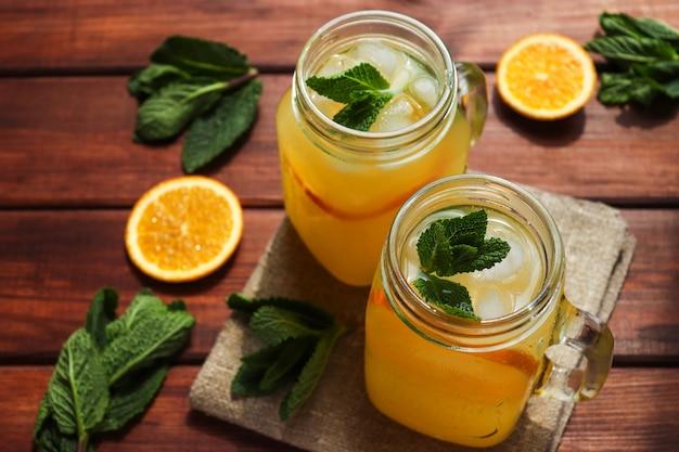 Limonade fraîche aux agrumes faite maison dans des bocaux avec de la menthe glacée et des oranges sur une table en bois boissons rafraîchissantes d'été