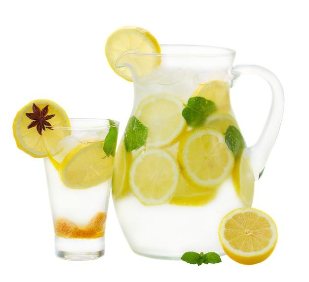 Limonade fraîche en pichet et grand verre isolé sur fond blanc