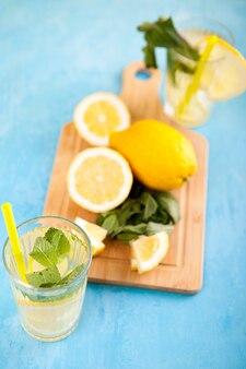 Limonade fraîche et savoureuse dans deux verres à côté de citrons coupés