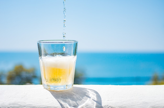 De la limonade froide est versée dans un verre.un verre de limonade rafraîchissante au fond