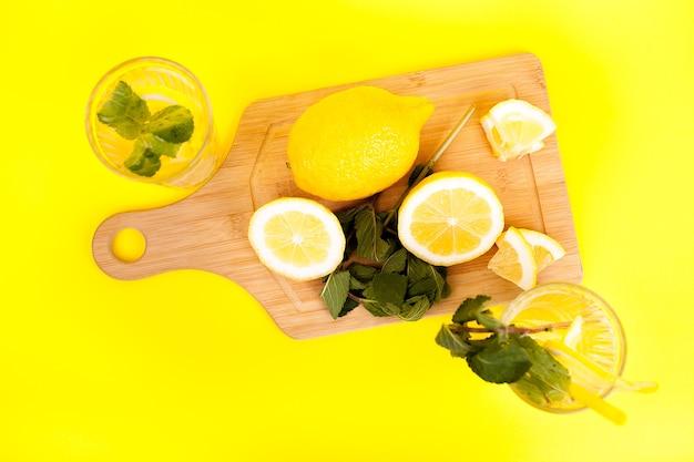 Limonade froide et savoureuse à base de citrons biologiques et frais sur fond jaune