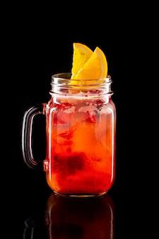 Limonade de fruits froids dans un bocal à conserves isolé sur fond noir