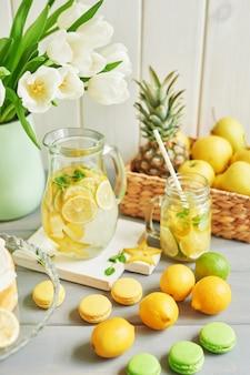 Limonade, fruits, macarons sucrés et fleurs de tulipes