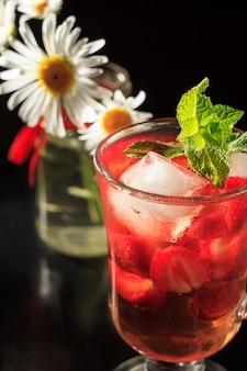 Limonade gazéifiée avec des tranches de fraise et menthe avec des fleurs de camomille sur fond noir. boisson froide pour les chaudes journées d'été