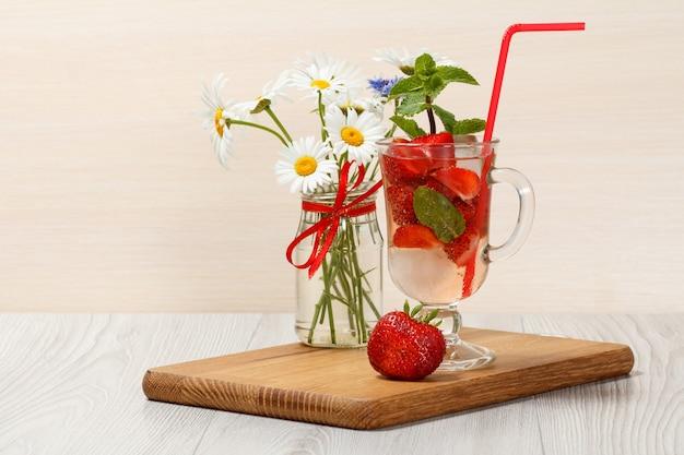 Limonade gazéifiée avec des tranches de fraises et de menthe sur une planche à découper en bois, boisson froide pour les chaudes journées d'été