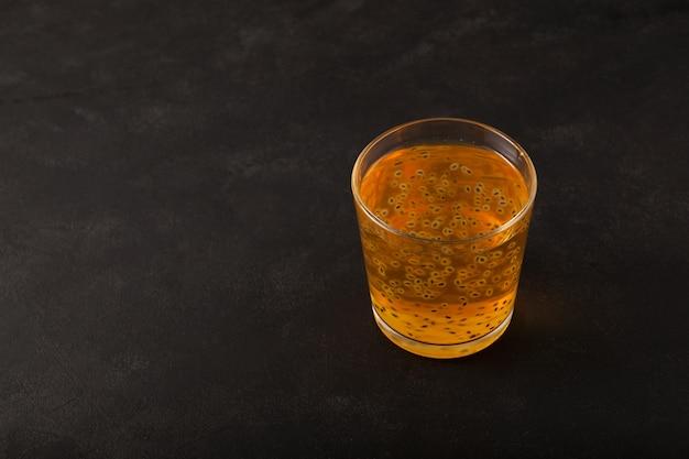 Limonade gélatineuse à la pêche ou cocktail aux graines de basilic sur fond texturé foncé