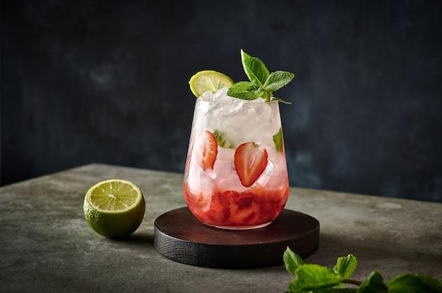 Limonade glacée fraîche faite maison avec des fraises citron vert et menthe sur une table en bois en bonne santé d'été