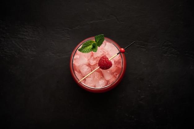 Limonade glacée fraîche faite maison avec la framboise et la menthe sur une boisson saine d'été de table en bois