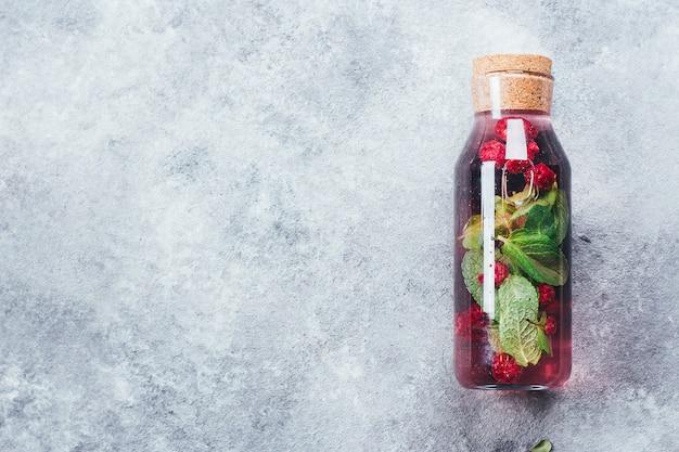 Limonade maison au cassis et à la menthe framboise dans une bouteille en verre. concept de boisson saine d'été