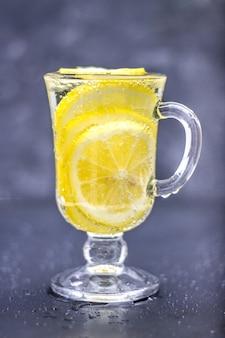 Limonade maison dans un verre avec une poignée sur un fond de béton gris. eau avec des tranches de citron