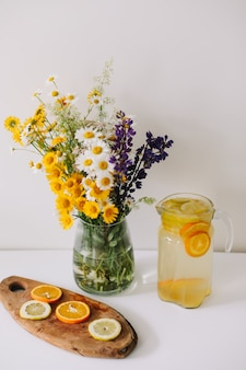 Limonade maison à l'orange et au citron et un bouquet de fleurs naturelles sauvages sur tableau blanc