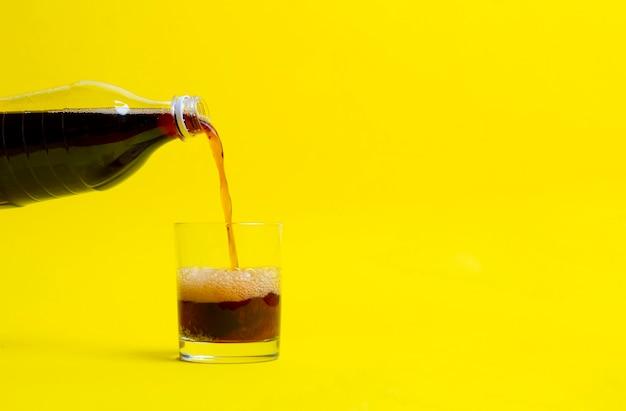 Une limonade noire versée dans le verre, bouteille de soda isolée sur fond de couleur