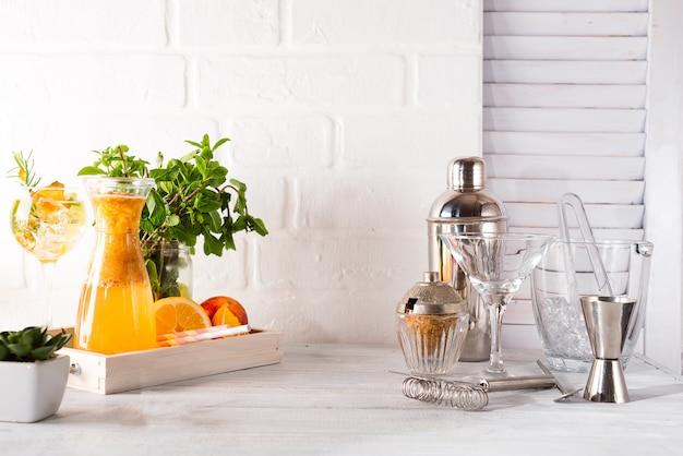 Limonade orange dans la carafe et le shaker avec une place pour votre sujet