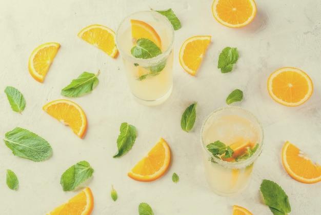Limonade orange et menthe fraîche avec de la glace dans des verres sur une table en marbre gris clair