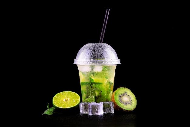 Limonade pour aller tasse à la menthe, citron vert et kiwi sur espace noir, isolé