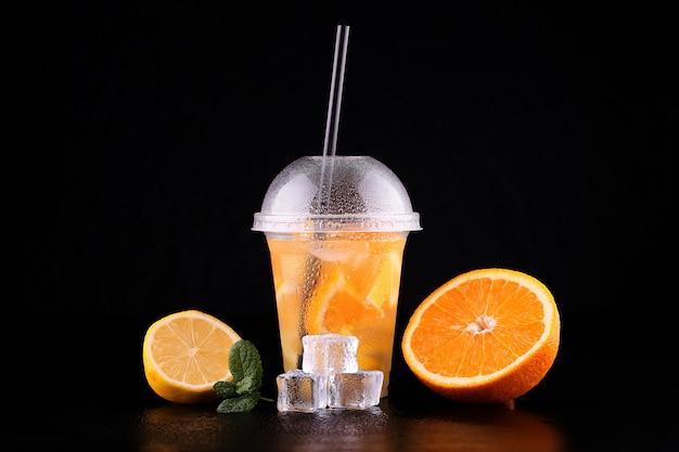 Limonade pour aller tasse à la menthe, orange et citron sur l'espace noir, isolé