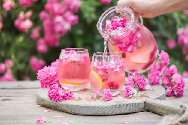 Limonade rose fraîche avec de la glace et des roses fraîches sur jardin naturel
